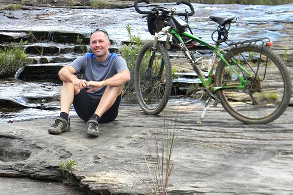 O cicloturista Nestor Freire posa para a foto em cachoeira em Carrancas